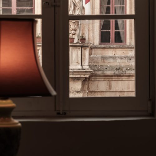 A warm photo of a lampshade in the Presidential Suite of The Xara Palace Relais & Chateaux overlooking the magnificent facade of the Mdina Local Council which housed the Maltese Law Courts in the past